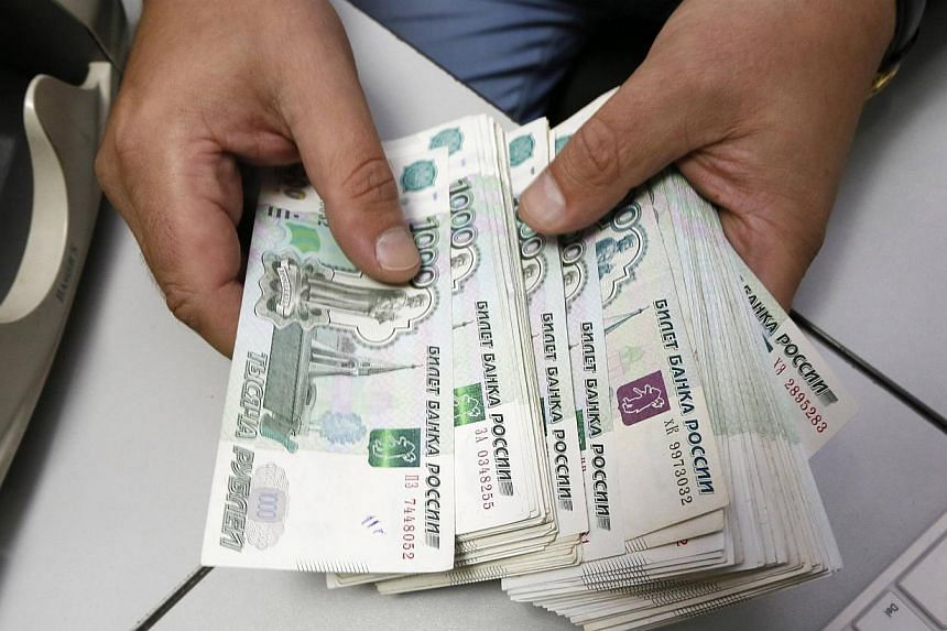 An employee counts Russian ruble banknotes at an office in Krasnoyarsk, Siberia, on Dec 17, 2014. -- PHOTO: REUTERS