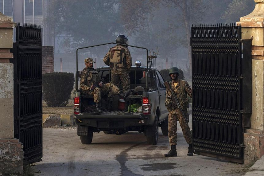 Soldiers yesterday entering the Army Public School which was attacked by Taleban gunmen in Peshawar. The gruesome attack took more than 140 lives - 132 of them children - marking a horrific moment even for a nation that is inured to extravagant viole