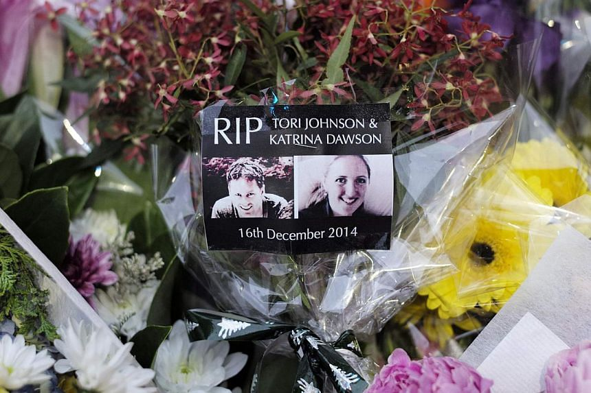 Images of the two victims who died in the Sydney cafe siege, lawyer Katrina Dawson (right) and Lindt store manager Tori Johnson, are pictured among floral tributes at a makeshift memorial before sunrise in Martin Place on Dec 18, 2014. -- PHOTO: REUT