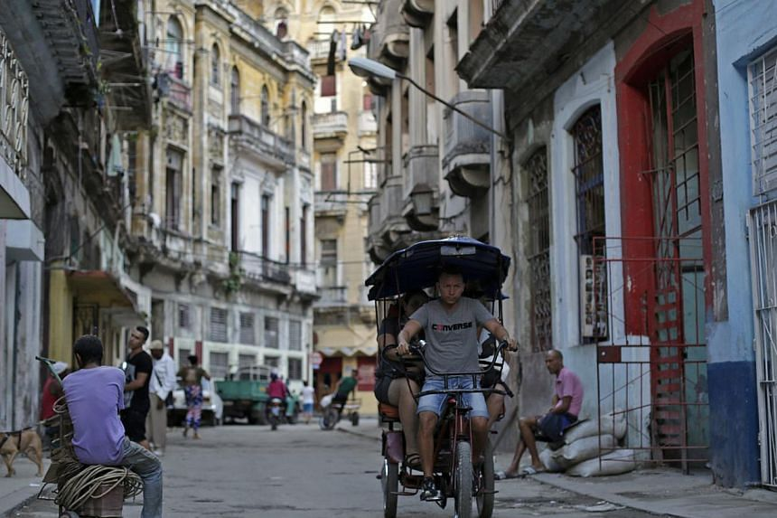 A man fetching passengers on his tricycle taxi in Havana on Dec 17, 2014. -- PHOTO: REUTERS