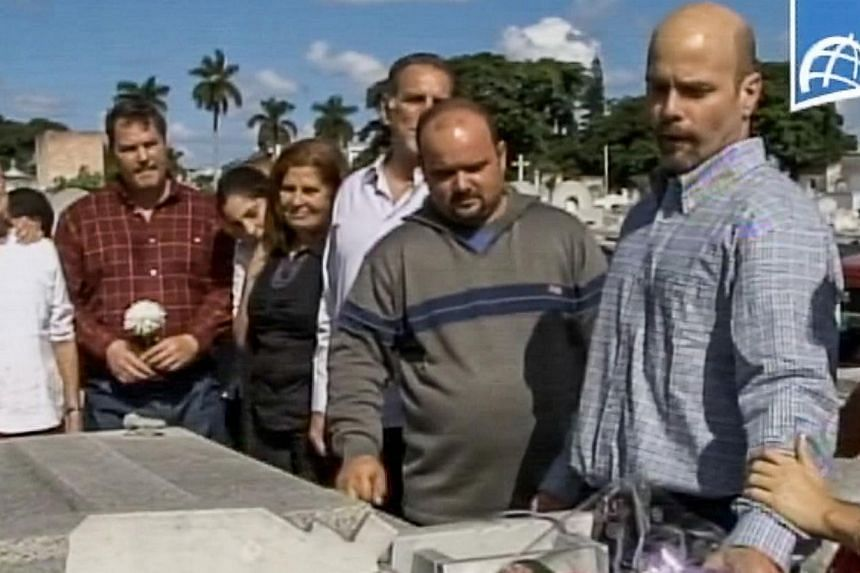 Freed Cuban prisoner Gerardo Hernandez (right) visiting a cemetery on Dec 17, 2014, in Havana on his return from the United States. -- PHOTO: AFP