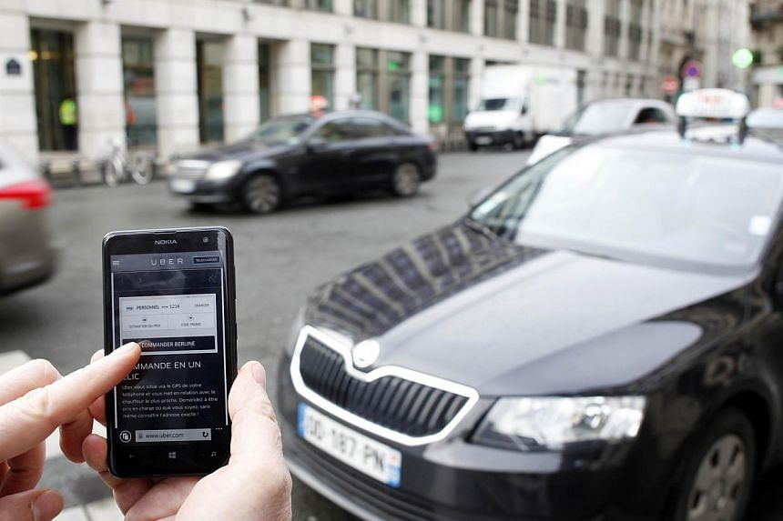 The Uber smartphone app being used used to book a taxi in Paris on Dec 10, 2014. Uber, which had a driver was accused of rape in New Delhi, said it was exploring adding new methods to verify drivers'credentials and make its service safer.