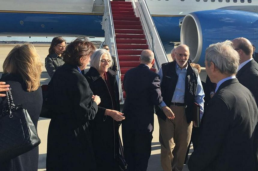 American aid worker Alan Gross (third right) disembarks with his wife Judy (fourth left) from a US government plane as he arrives at Joint Base Andrews, Maryland outside Washington Dec 17, 2014 in this photo tweeted by US Senator Jeff Flake. -- PHOTO