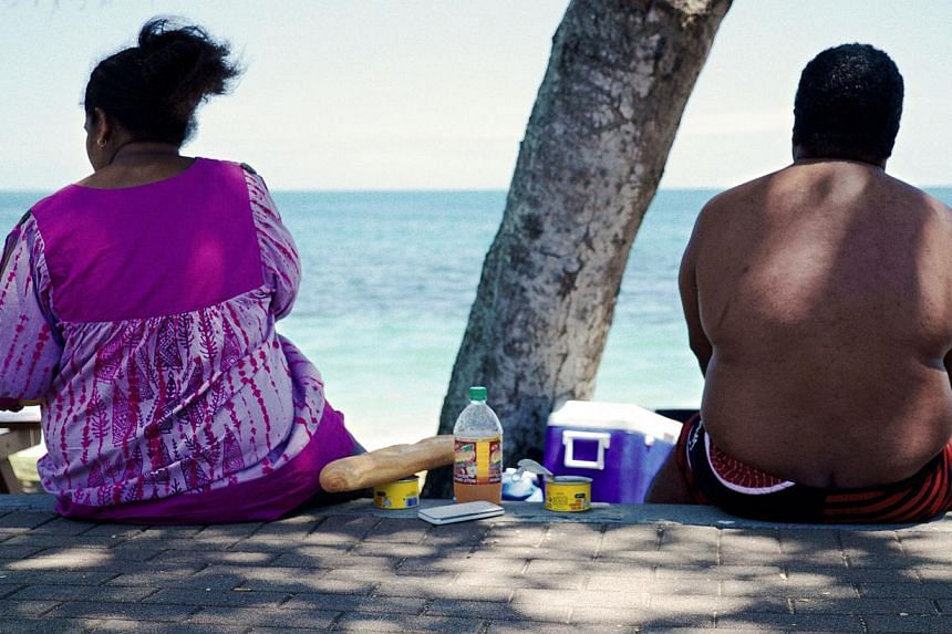 People sit along the beach looking out at sea in Noumea on Dec 1, 2014. -- PHOTO: AFP