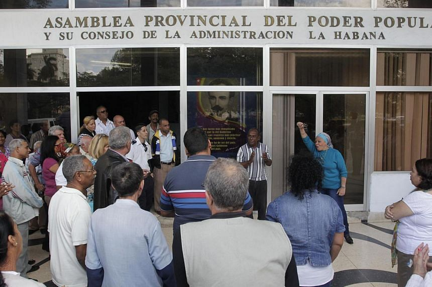 People gather outside a building of the Provincial Assembly of the People's Power for news updates, in Havana Dec 17, 2014.The renewal of full diplomatic relations between the United States and Cuba could be the start of a long thaw in decades