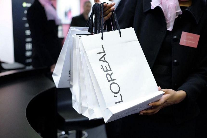 An employee gives bags to visitors at the stand of French cosmetics giant L'Oreal during the Actionaria shareholders fair in Paris on Nov 21, 2014. -- PHOTO: AFP