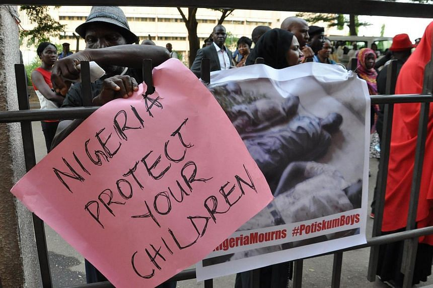 A civil society group carrying posters march on Nov 17, 2014 to protest the killing of over 47 students of Portiskum Government Comprehensive School in Yobe State, during an Assembly ground on Nov 10, 2014. -- PHOTO: AFP
