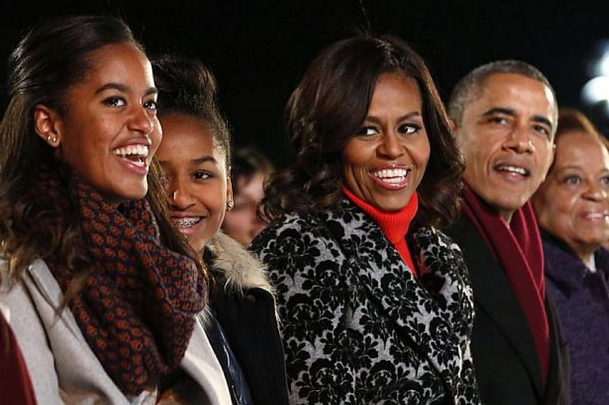 US President Barack Obama and his family (from left), daughters Malia and Sasha, First Lady Michelle Obama and mother-in-law Marian Robinson, attend the lighting of the National Christmas Tree near the White House in Washington, Dec 4, 2014. Barack a