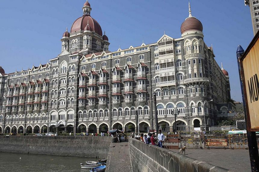 Tourists sit in front of the Taj Mahal hotel, which was one of the targets of the Nov 26, 2008 attacks, in Mumbai on Nov 26, 2014. -- PHOTO: REUTERS