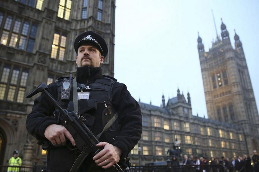 An armed police officer stands outside the Houses of Parliament, central London Nov 26 , 2014.Police looking into accusations that powerful figures at the heart of the British establishment were involved in child sex abuse in the 1970s and 1980