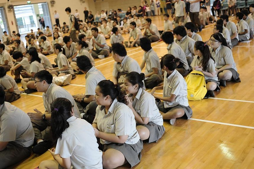 Students at Bedok Green Secondary School waiting to get the results for their N-level examinations on Dec, 17 2012. More students did well enough at the N-levels this year to make the cut for Secondary 5. -- PHOTO: ST FILE