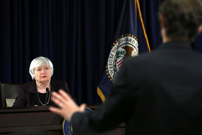 A reporter asks a question during a news conference held by US Federal Reserve cchairman Janet Yellen (left) at the Federal Reserve in Washington Dec 17, 2014. -- PHOTO: REUTERS