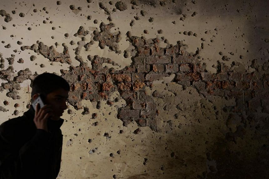 A student walks past a bullet-riddled wall inside the army-run school. Pakistan's military said on Friday that it had killed 32 militants in clashes in a troubled tribal region near the Afghan border, days after the Taleban massacre killed 148 people