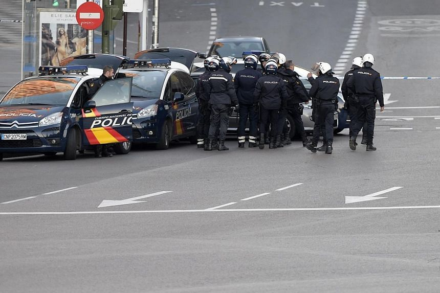 Spanish policemen and bomb disposal experts gather outsidethe headquarters of Spain's ruling People's Party after a man runned his car with two gas cylinders into the buidling, in Madrid on Dec 19, 2014. -- PHOTO: AFP