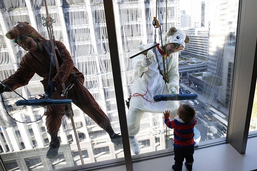 Window cleaners, dressed in horse (left) and sheep costumes featuring animals from the Chinese zodiac calendar, work during an event promoting the year-end and new year at a hotel in the business district of Tokyo on Dec 19, 2014. The year of 2014 is