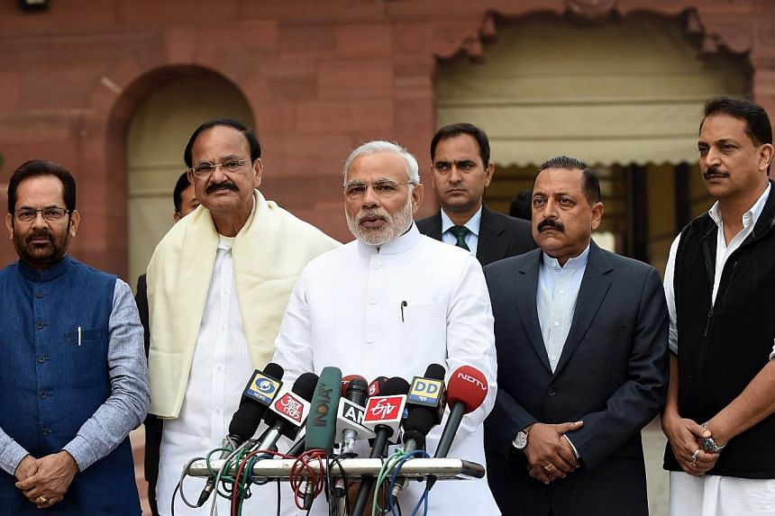 Indian Prime Minister Narendra Modi (centre) addresses the media as Minister of State for Parliamentary Affairs Mukhtar Abbas Naqvi (left), Urban Development Minister Vankaiah Naidu (second, left), Minister of State (PMO) Jitender Singh (second, righ