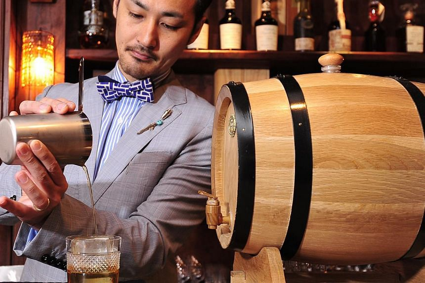 Owner-head bartender Daiki Kanetaka (above) of D.Bespoke and a drink called The Godfather, made from a mixture of Yamazi 12 whisky and Amaretto. -- PHOTO: DIOS VINCOY JR FOR THE STRAITS TIME
