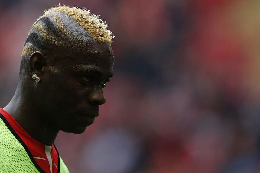 Liverpool striker Mario Balotelli (above) has been suspended for one match, fined £25,000 (S$51,000) and ordered to attend to an education course after making racist and anti-semitic comments. -- PHOTO: REUTERS