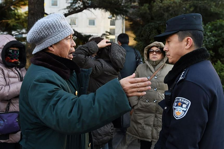 A relative of a passenger from missing Malaysia Airlines flight MH370 speaks with a policeman outside the Foreign Ministry in Beijing on Dec 19, 2014. -- PHOTO: AFP