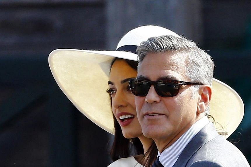 George Clooney (right) and his wife Amal Alamuddin leave Venice city hall after a civil ceremony to formalise their wedding in Venice, Italy on Sept 29, 2014. Clooney has stood up to criticise Hollywood for not rallying behind Sony Pictures as it was
