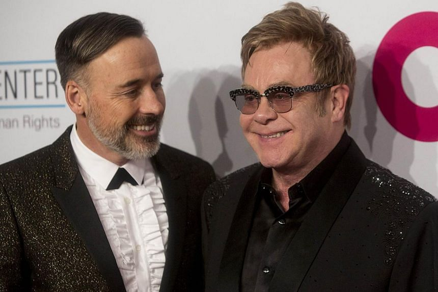 David Furnish (left) and Sir Elton John attend an Elton John Aids Foundation benefit in New York on Oct 28, 2014. Pop icon Elton John will wed his partner of more than 20 years this weekend in England, reports said. -- PHOTO:REUTERS