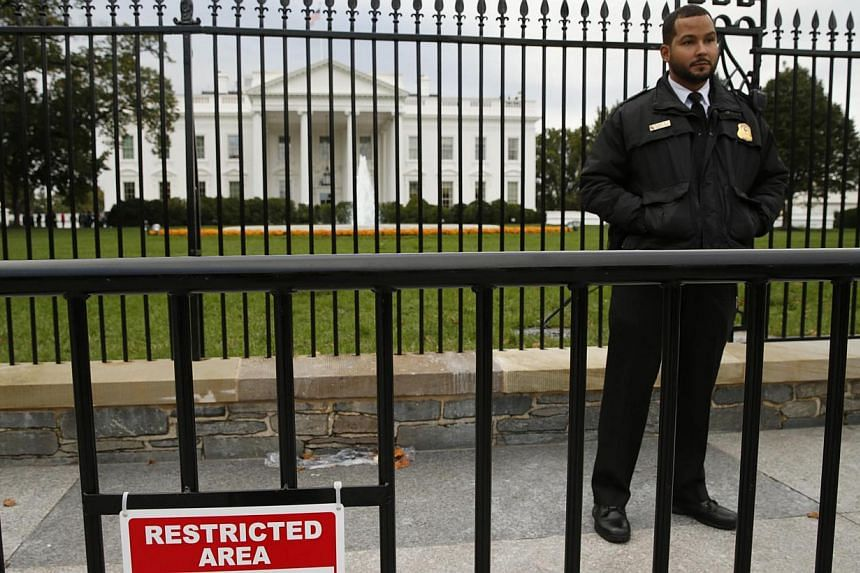 A member of the US Secret Service stands guard in front of the North Lawn of the White House in Washington Oct 23, 2014.The White House fence should be immediately raised by four or five feet (1.2m to 1.5m), according to an independent se