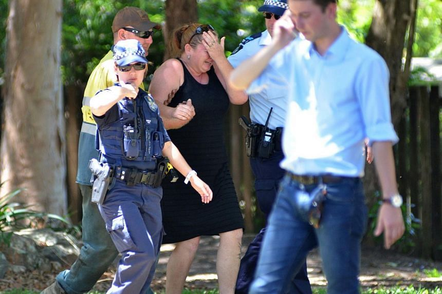 Police comforting a distressed woman at the scene where eight children aged between 18 months and 15 years were found dead at a home in the northern Australian city of Cairns, the police said on Dec 19, 2014, reportedly after a gruesome mass stabbing