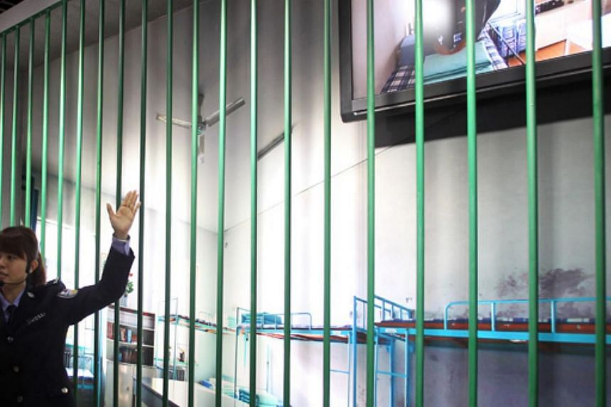 A member of staff at the Anti-Corruption Education Centre in the Daxing district of Beijing showing visitors a picture of prison cell. Similar centres have been opened across the country. -- PHOTO: CHINA DAILY/ASIA NEWS NETWORK