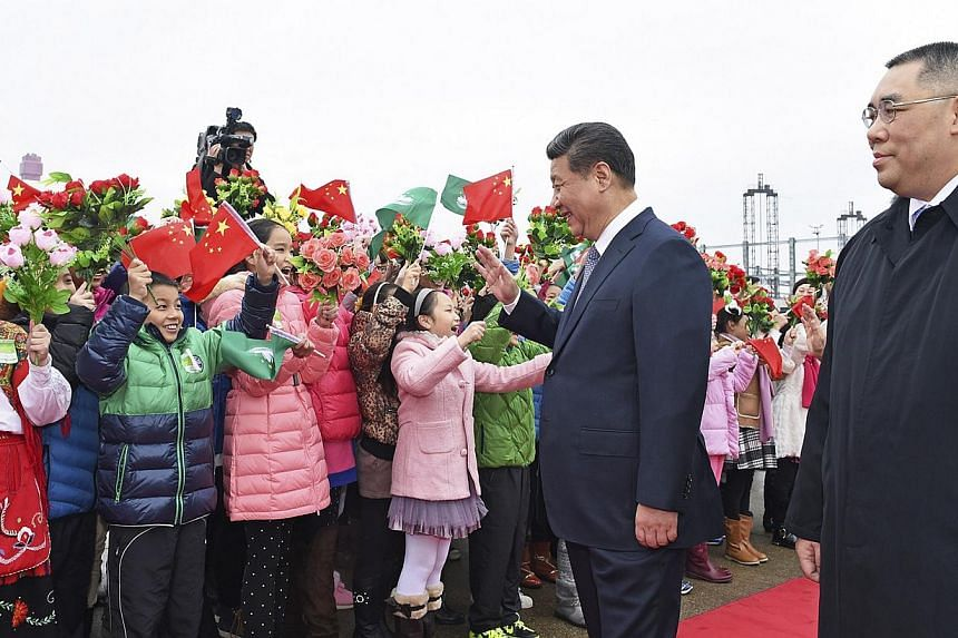 Chinese President Xi Jinping (2nd right) waves to children waving Chinese national flags and the flag of Macau, as Macau Chief Executive Fernando Chui Sai-On watches, after Xi arrived in Macau to celebrate the 15th anniversary of its handover to the