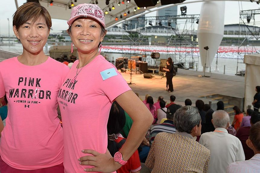 (Left to right) Ms Katherine Goh and Ms Irene Chui, from the Breast Cancer Foundation, were among those who wrote wishes on spheres to be tossed into Marina Bay. -- ST PHOTO: DESMOND WEE