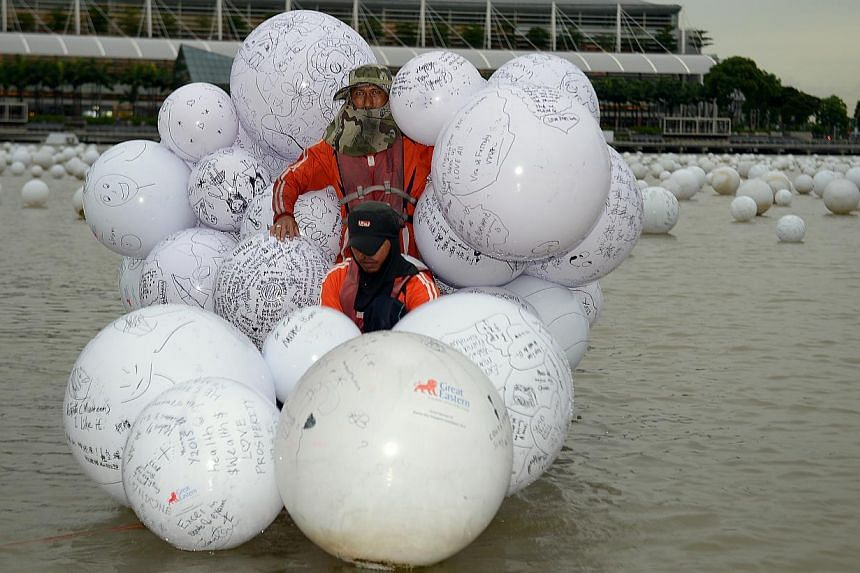 Picture of people tossing balls, plus of some of the beneficiaries who will be penning their well wishes for Singapore onto floating balls and then throwing them into Marina Bay. -- ST PHOTO: DESMOND WEE