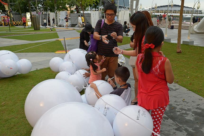 Picture of people tossing balls, plus of some of the beneficiaries who will be penning their well wishes for Singapore onto floating balls and then throwing them into Marina Bay.-- ST PHOTO:DESMOND WEE