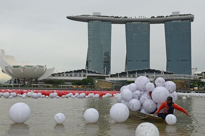 Staff collecting the wishing spheres that were tossed into Marina Bay by beneficiaries, to be arranged into the pattern of a giant 50 with the other spheres. -- ST PHOTO:DESMOND WEE