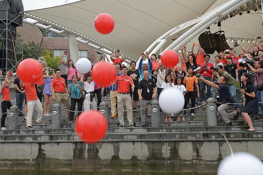 Dr Khoo Kah Siang, CEO of Great Eastern Life with Benson Puah, CEO of the Esplanade, along with 12 representatives from six voluntary welfare organisations, toss wishing spheres into Marina Bay. -- ST PHOTO: DESMOND WEE