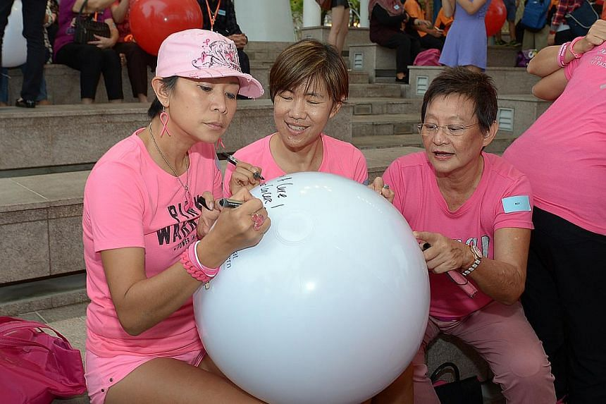 (Left to right) Ms Irene Chui, Ms Katherine Goh and Ms Esther Sim, from the Breast Cancer Foundation, writing their wishes on spheres to be thrown into Marina Bay. -- ST PHOTO: DESMOND WEE
