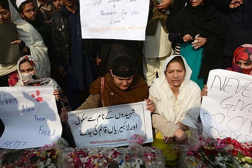Pakistan civil society activists hold placards during a protest against the Taleban militants' attack on an army-run school in Peshawar on Dec 18, 2014. -- PHOTO: AFP