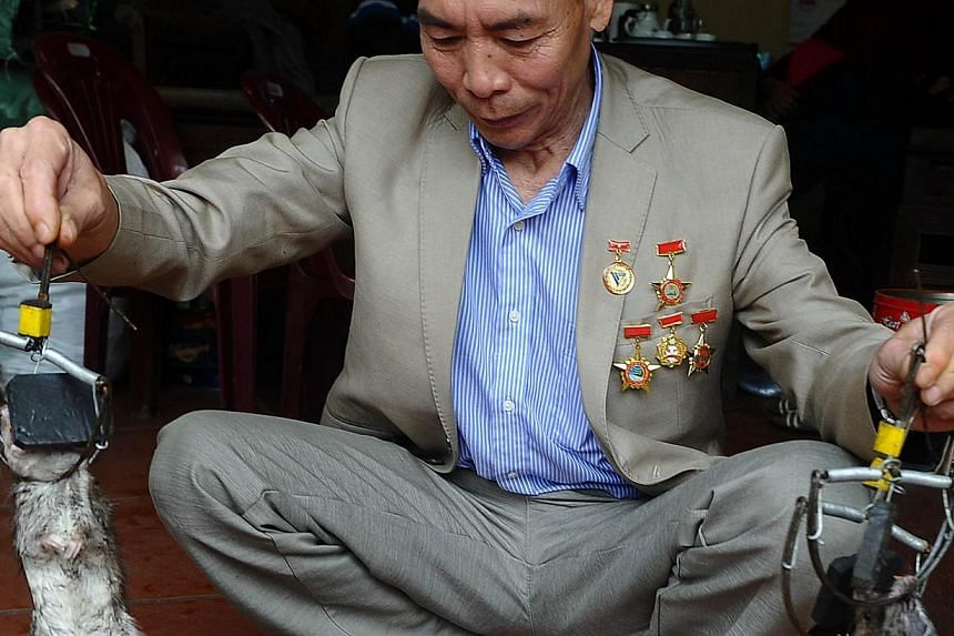 """Mr Tran Quang Thieu, nicknamed """"Rat King"""", explaining features of a rat trap he has created at his home on the outskirts of Hanoi on March 3, 2014. -- PHOTO: AFP"""