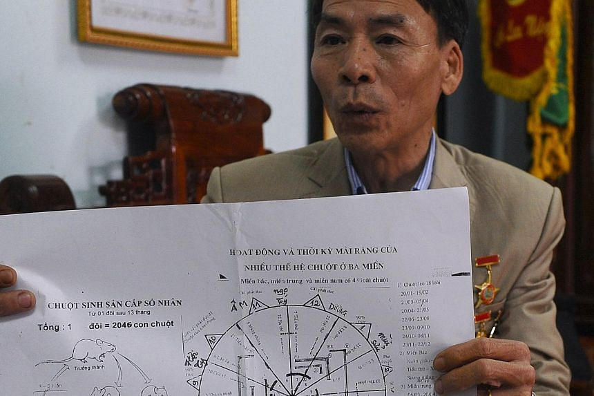 Mr Tran Quang Thieu explaining how to trap rats at his home on the outskirts of Hanoi on March 3, 2014. -- PHOTO: AFP