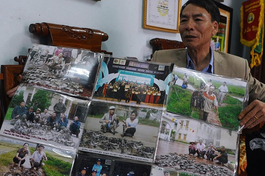 Mr Tran Quang Thieu shows photographs of his rat-killing records in different areas in Vietnam during an interview with AFP at his home on the outskirts of Hanoi on March 3, 2014. -- PHOTO: AFP  P