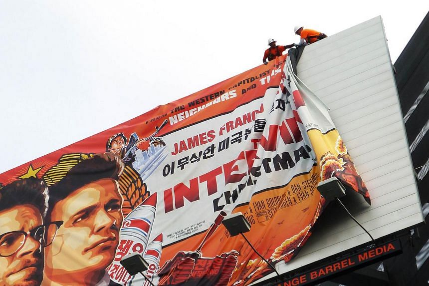 Workers remove the poster for The Interview from a billboard in Hollywood, California, Dec 18, 2014, a day after Sony announced it had no choice but to cancel the movie's Christmas release and pull it from theatres due to a credible threat. -- PHOTO: