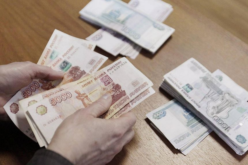 An employee of a local company, producing equipment for electrical meters, counts Russian rouble banknotes in Stavropol, southern Russia on Dec 17, 2014. -- PHOTO: REUTERS