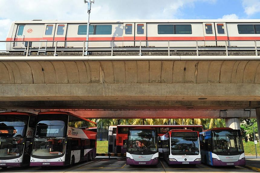 SBS buses parked under the SMRT track while an SMRT train passes by the Yio Chu Kang bus interchange on July 21, 2014. Both public transport operators SMRT and SBS Transit have submitted their applications for fare adjustments to the Public Tran