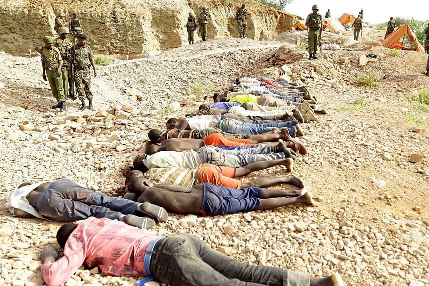Members of the military gather near the bodies of some 36 quarry workers killed by Shebab rebels on Dec 2, 2014 near the town of Mandera, northern Kenya, along the border with Somalia. A Finnish court on Friday handed suspended jail terms to four men