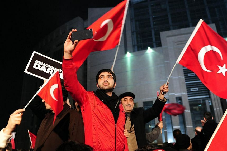 Supporters of Zaman daily newspaper wawe Turkish flags outside Istanbul's courthouse during a protest against the hugely controversial raids targeting Zaman newspaper and television channel linked to US-based Muslim cleric Fethullah Gulen on Dec 18,