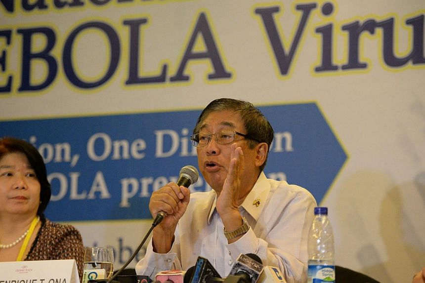 Mr Enrique Ona (right), Philippine Health Secretary gestures as he speaks at a press conference during the national Ebola virus summit in Manila on Oct 10, 2014, while Ms Socorro Lupisan, head of research institute for topical medicine listens. -- PH