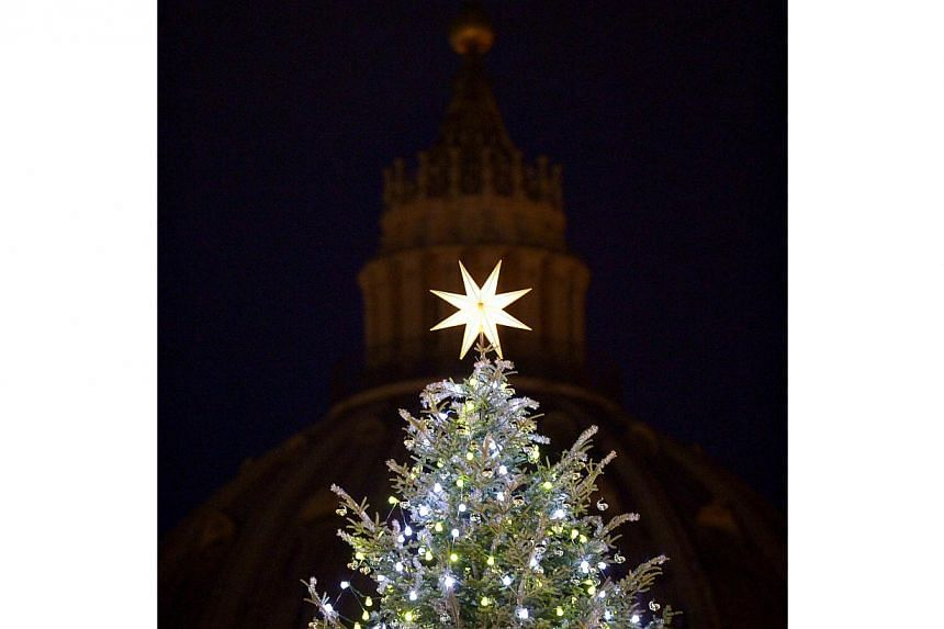 The Christmas pine tree in front of Saint Peter's basilica after it was illuminated during a ceremony. -- PHOTO: AFP
