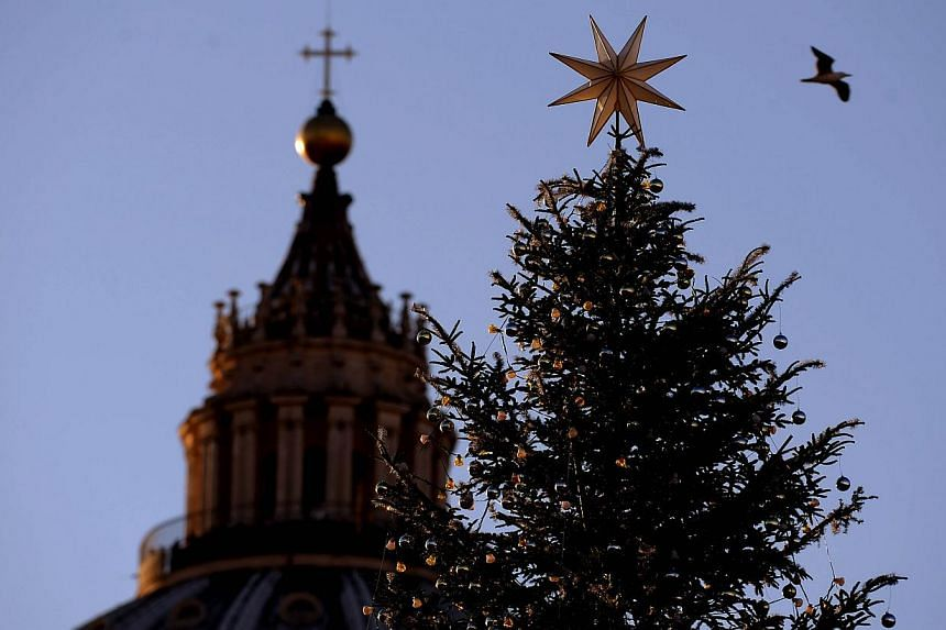 A silhouette of the Christmas pine tree set in front of St Peter's basilica is on Dec 19, 2014, before a lighting-up ceremony. -- PHOTO: AFP