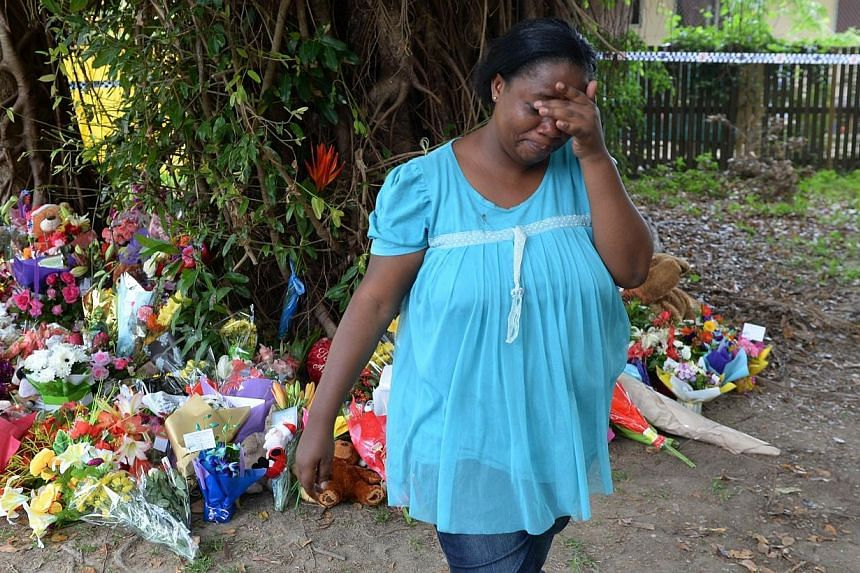 A woman cries after laying flowers on Dec 20, 2014 at the scene where eight children ranging from babies to teenagers were found dead in a house in the northern Australian city of Cairns.The police have confirmed that the children reporte