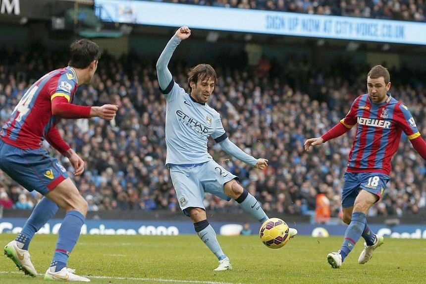 Manchester City's David Silva (centre) shoots to score his second goal against Crystal Palace during their English Premier League soccer match at the Etihad Stadium in Manchester, northern England Dec 20, 2014. -- PHOTO: REUTERS