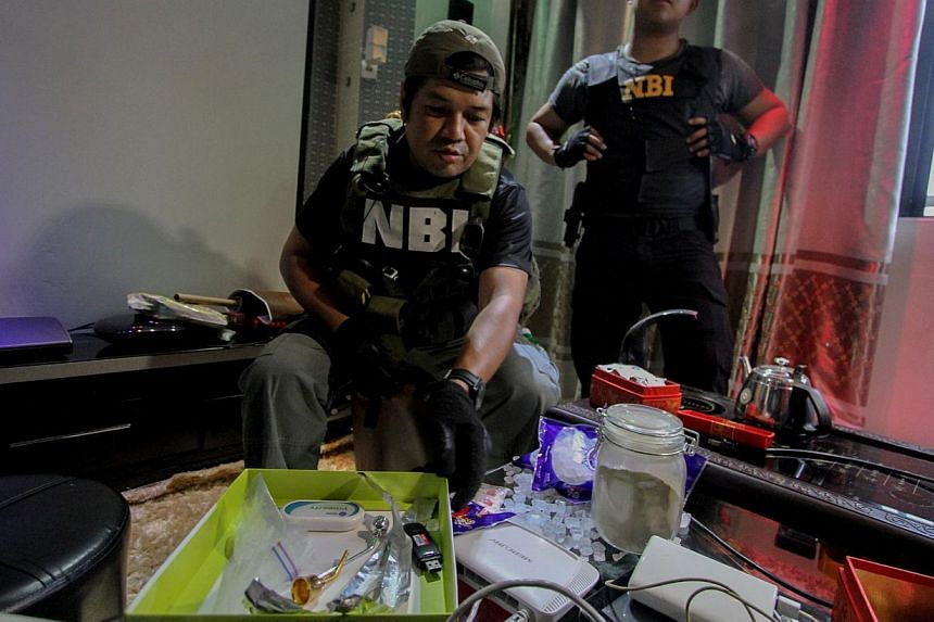 National Bureau of Investigation operatives inspect confiscated materials inside the Bilibid prison in Muntinlupa, south of Manila on Dec 16, 2014. -- PHOTO: AFP